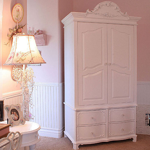 mary claire armoire shown in swiss coffee finish with decorative crown molding and vintage beading around rawer fronts with glass knobs