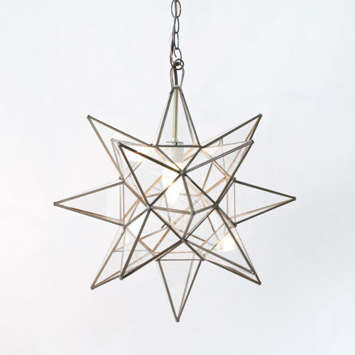 close up of 3 dimensional star glass pendant with clear glass and brass trim