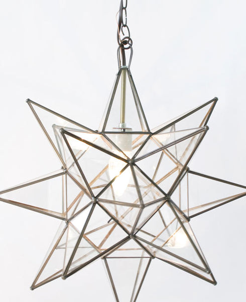 close up of three dimension star glass pendant with clear glass and brass trim