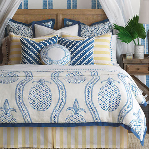 sunshine blue pineapple duvet is mixed together with blue and white throw pillows and yellow and white striped shams and bedskirt