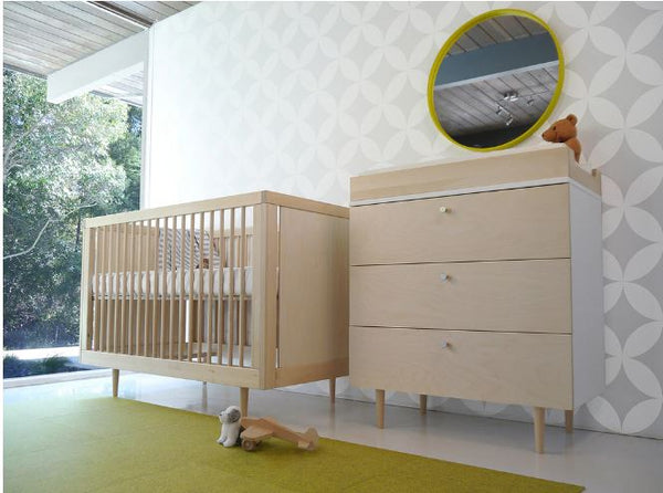 altman crib shown in birch with green rug and changing table station with green mirror above
