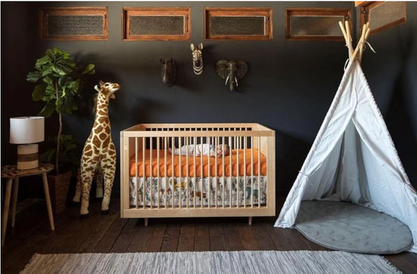 altman crib shown in jungle nursery with black walls and teepee with baby laying in crib