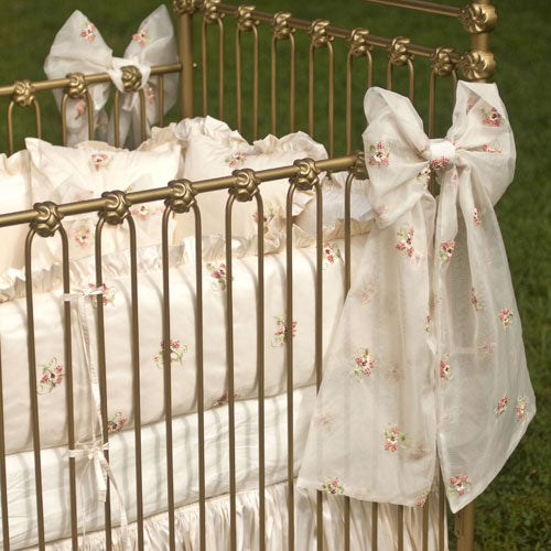 close up of baby bedding shown on crib showing large silk bow tied on gold crib
