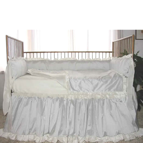 delphine baby bedding shown on gold iron crib with delicate ruffle at the top and bottom of skirt with ruffle trim on the top of crib bumper and on blanket all shown in white