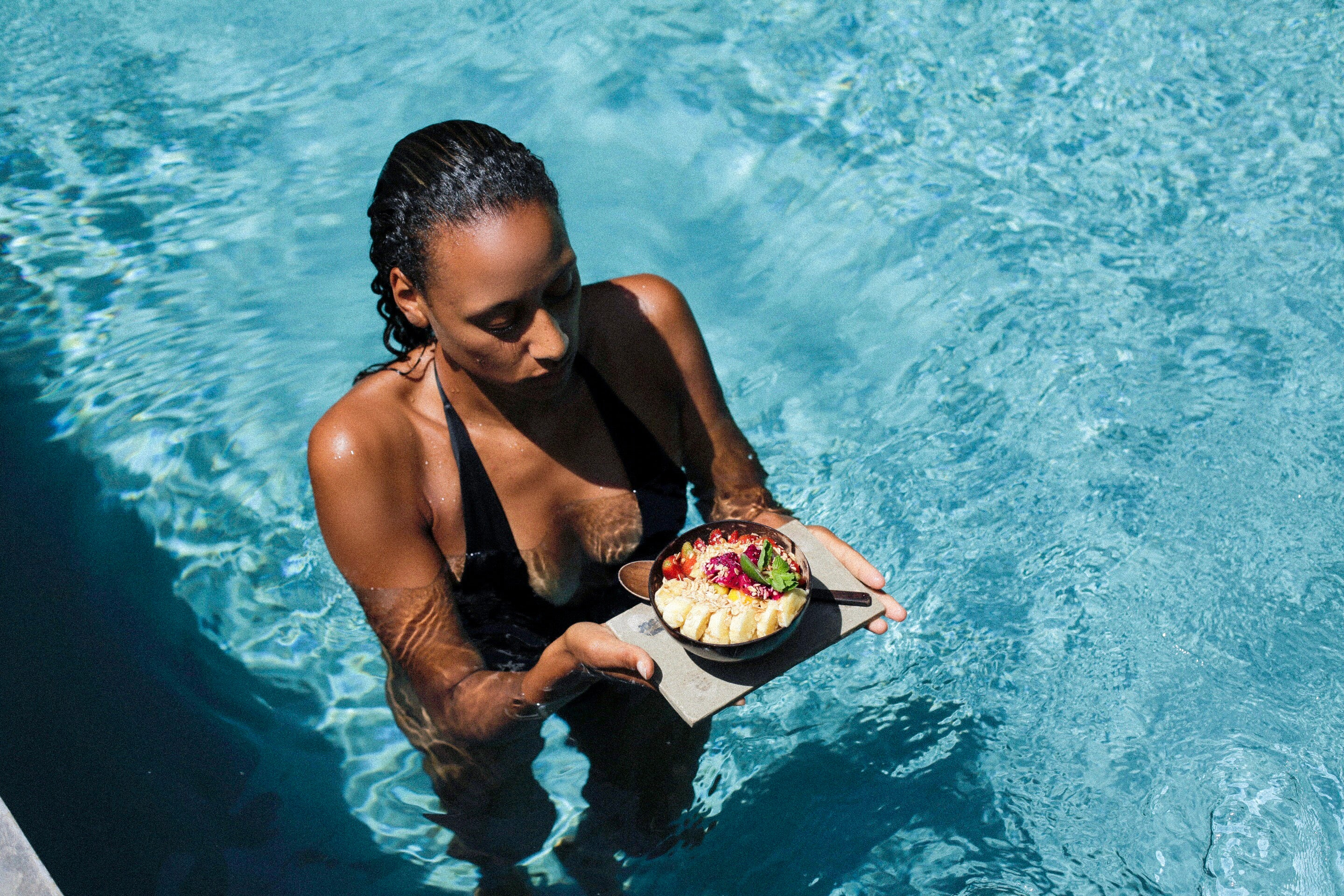 Jasmine Sjoberg Sidibe in a pool with a bowl of fruit