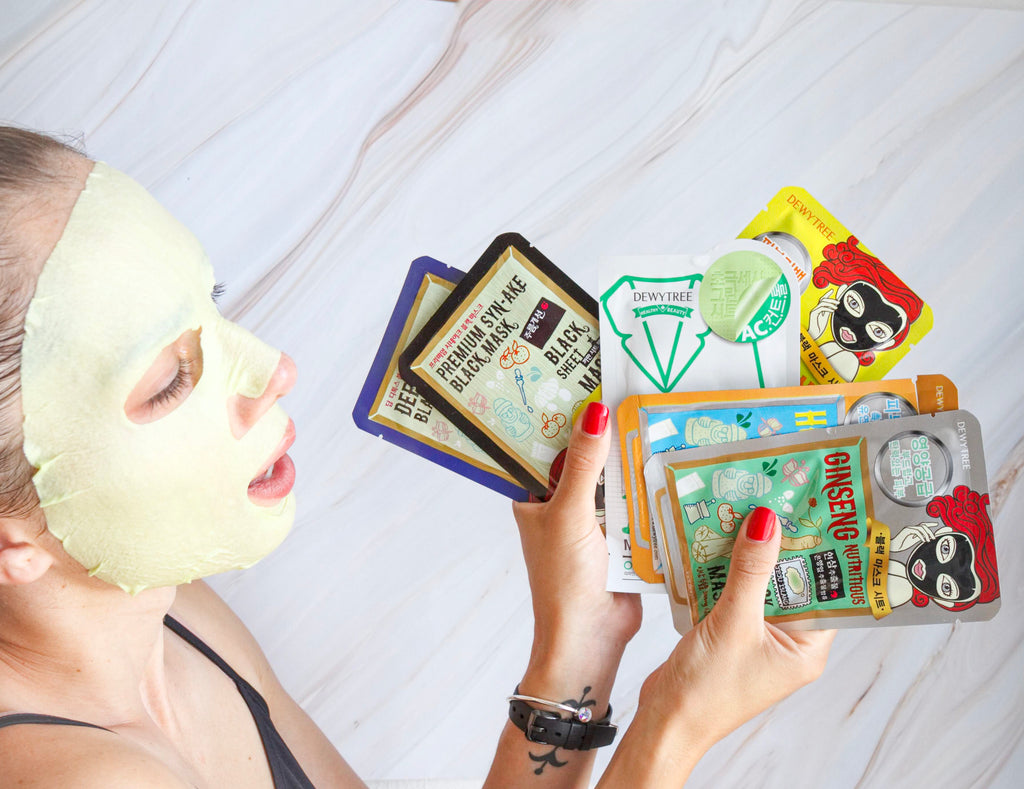 Girl with a sheet mask, holding a selection of sheet masks for acne, hydration, anti-aging and glow
