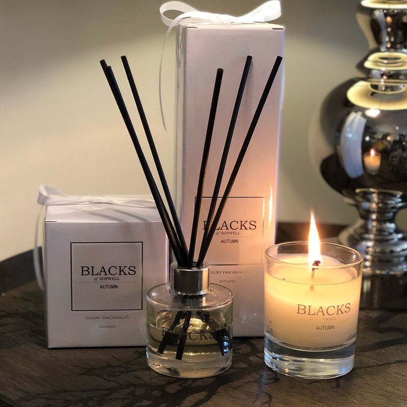 blacks autumn diffuser shown with lit autumn candle.  white packaging tied with a white ribbon.
