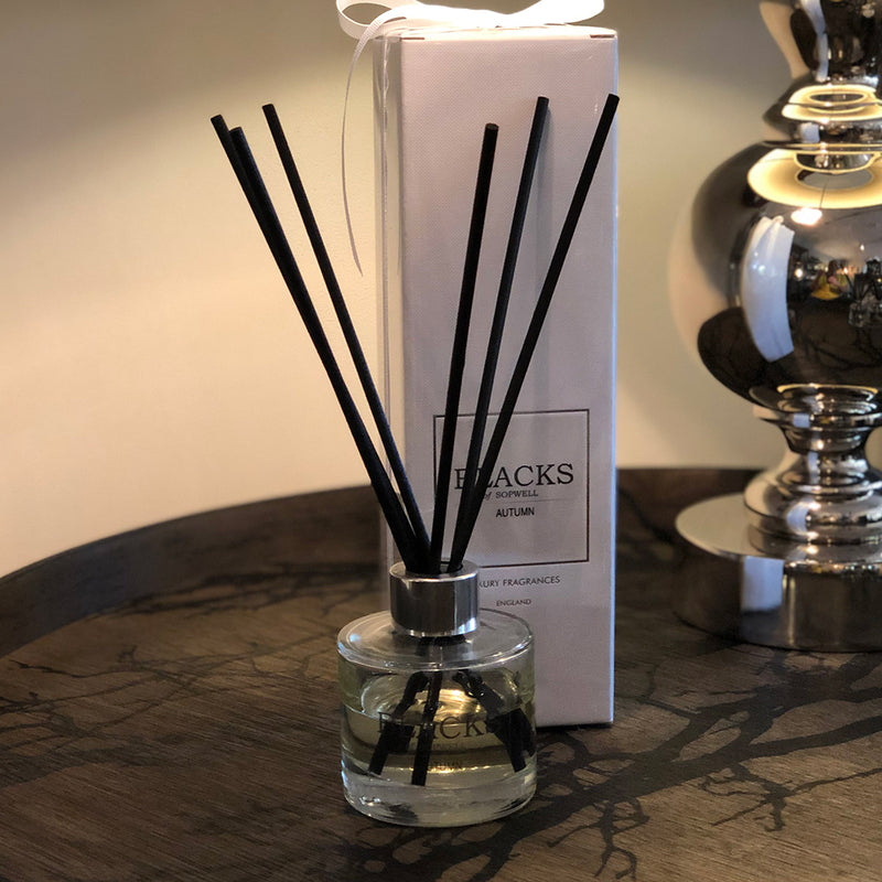 Blacks Autumn Diffuser, clear glass base with clear label. black writing,black reed sticks. White packaging shown next to it with white ribbon