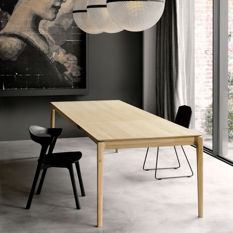B1 table shown in contemporary home, with black chairs.side angle shows the smooth rounded leg.