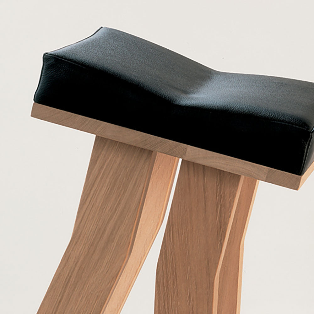 detail of black leather seat , dipped in the middle, on an oak frame
