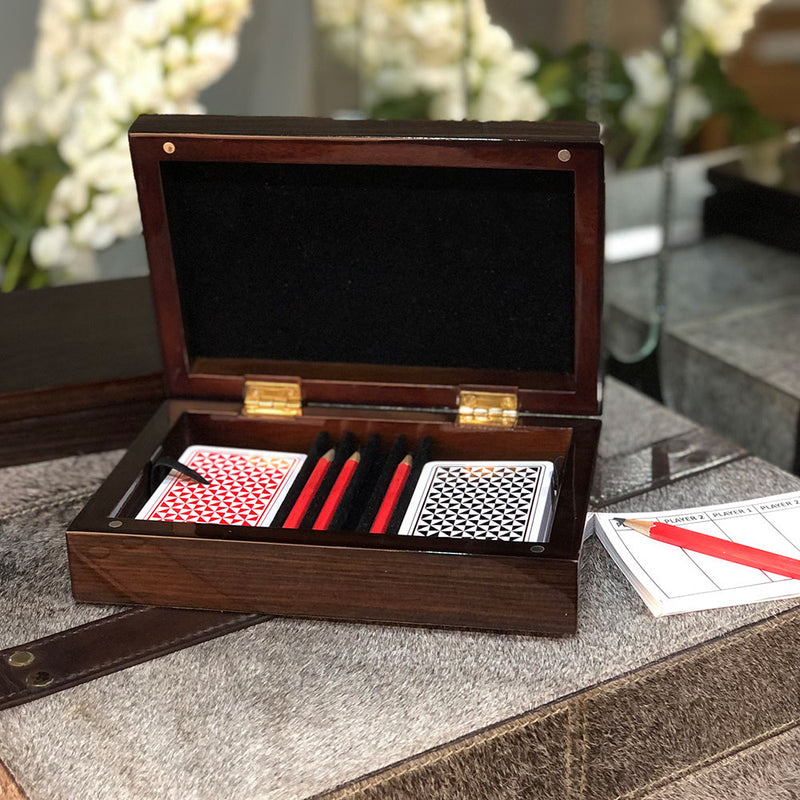 brown walnut box with magnetic close, 4 red pencils, 2 packs of playing cards and a score pad.