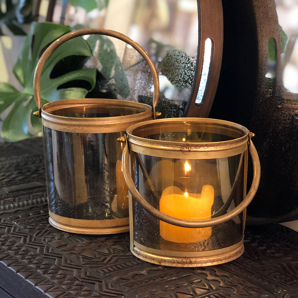 burnished gold hurricane with pillar candle burning inside .