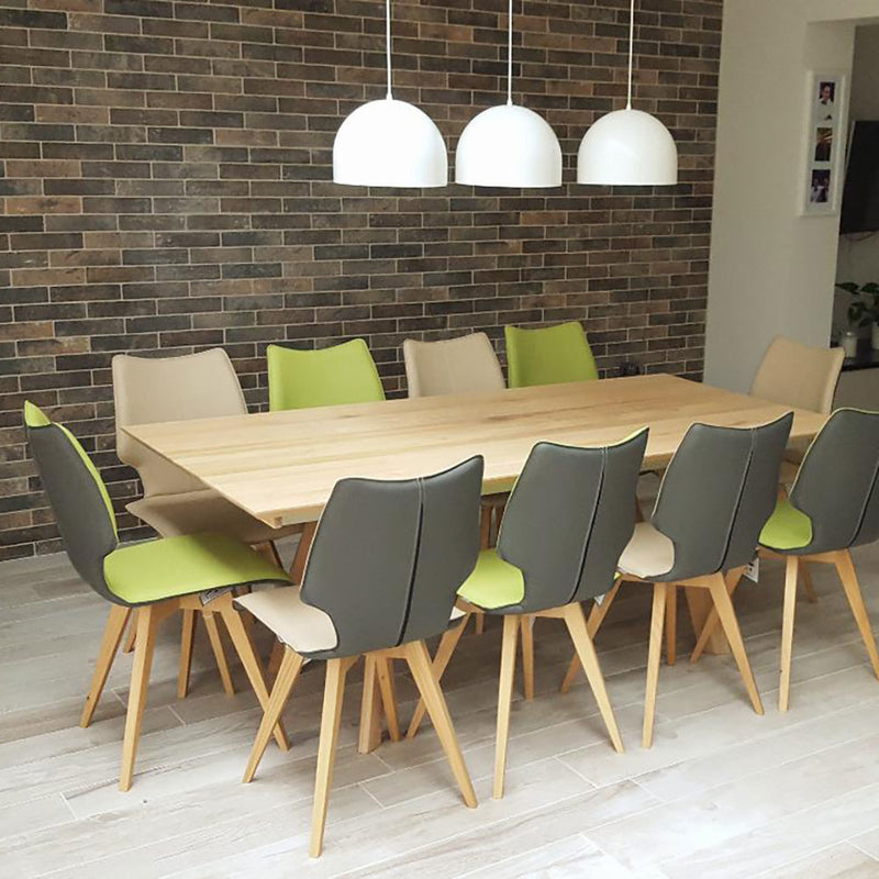 set of c1 chairs arroung oak table in contemporary dining room. all grey backs, alternating lime and sand colour fronts.
