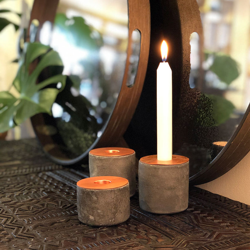 chunk candle holder- concrete base with copper top, shown with lit taper candle