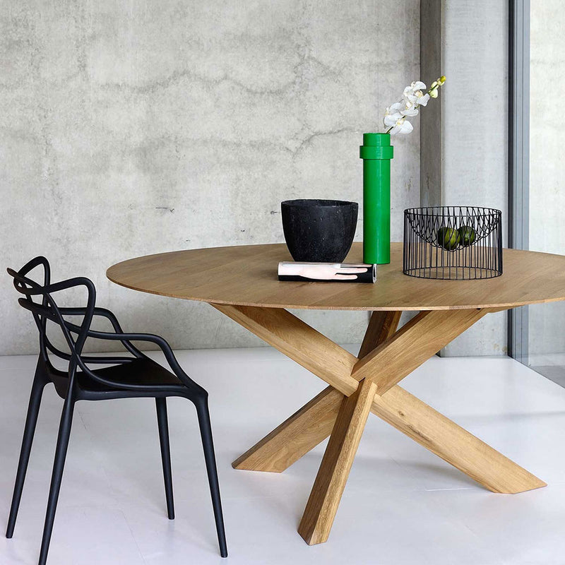 Circle table in solid oak shown with dining chair and styles with fruit bowl and vase on table