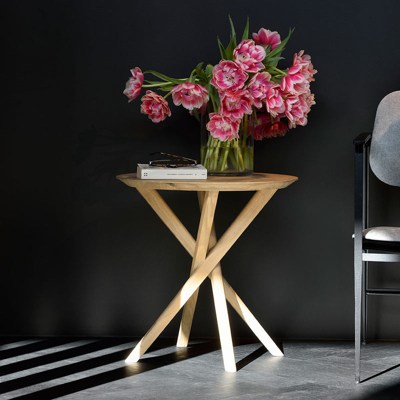 elements solid oak side table with round top and crossed  legs, shown with vase of flowers on top.