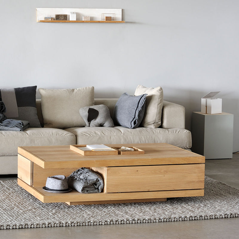 Flat coffee table, showing drawer front and open shelf underneath, set in contemporary living room.