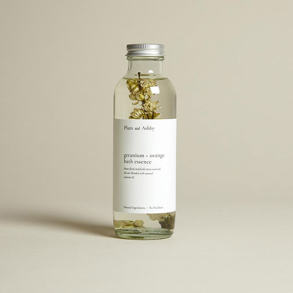 Glass clear bottle with silver lid and white label. clear bath essence with a sprig of dried geranium flower inside.