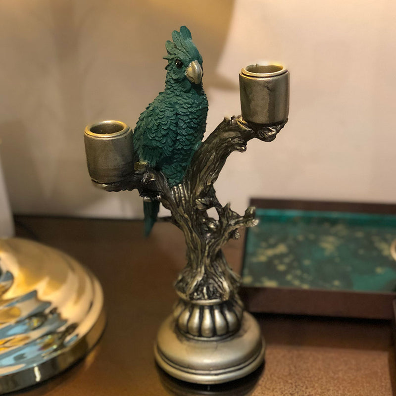 green cockatoo perched on gold candlestick for two candles