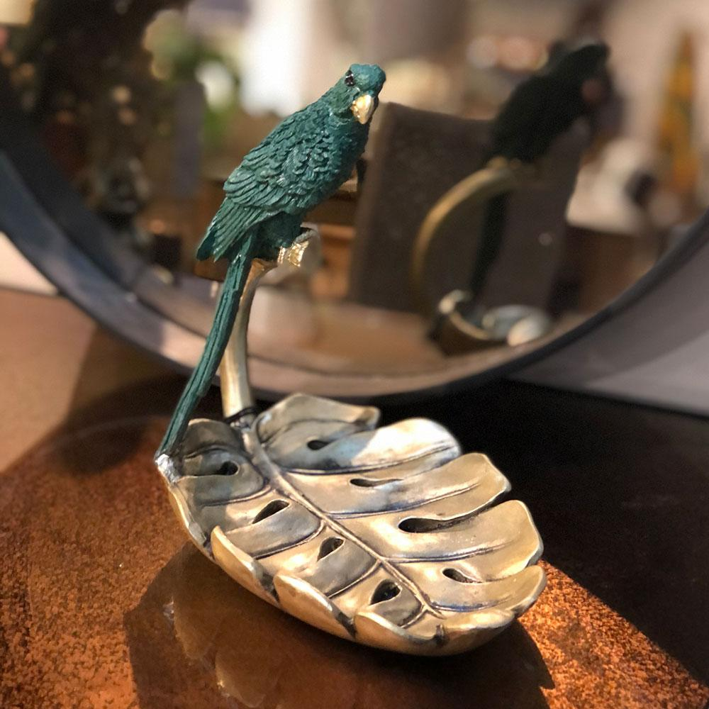 resin gold palm dish with parrot sitting on the curled stem