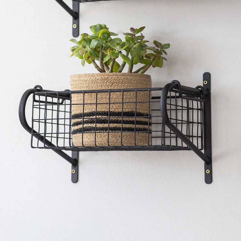 small black metal rectangular basket hanging from wall brackets