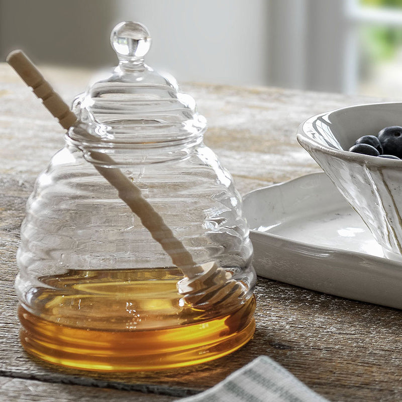 glass honey pot shaped jar, with beech wood dibber, shown with honey inside