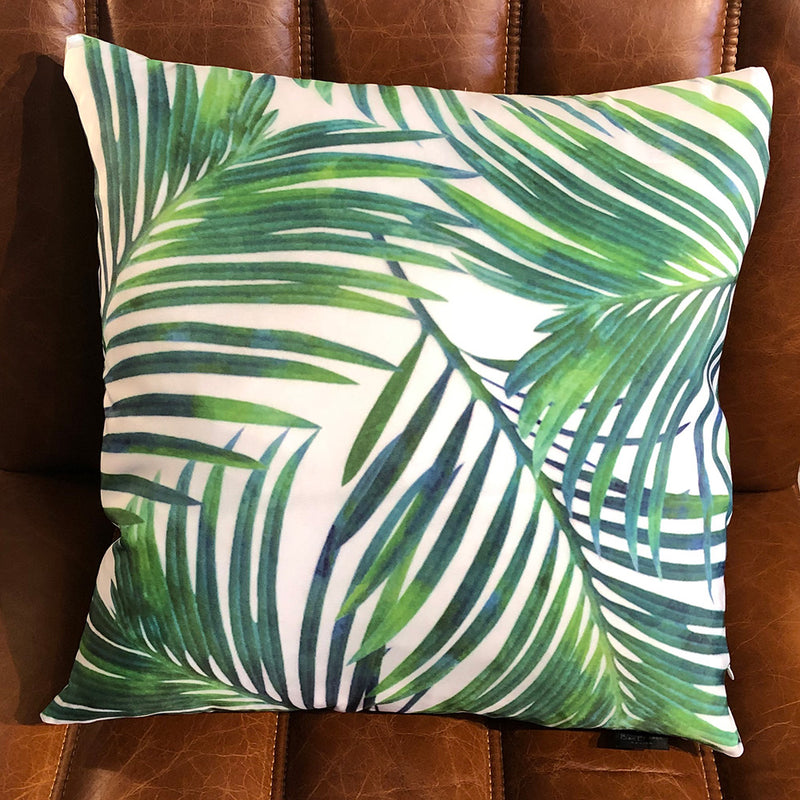 green palm leaves against white handmade cushion front
