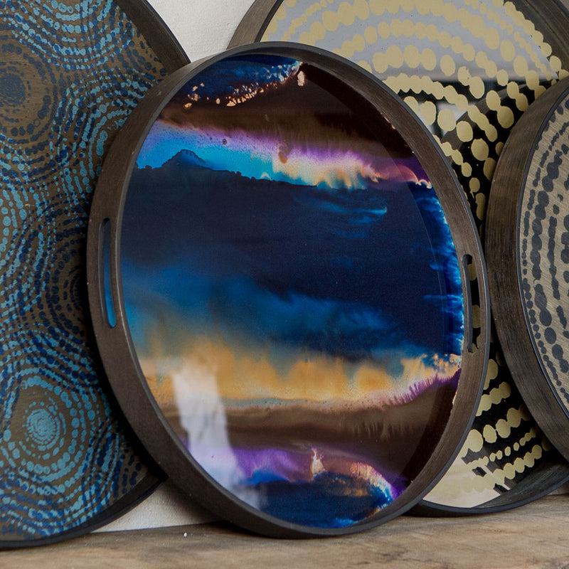 small round tray with glass bottom. under glass is painted purple blue gold and brown
