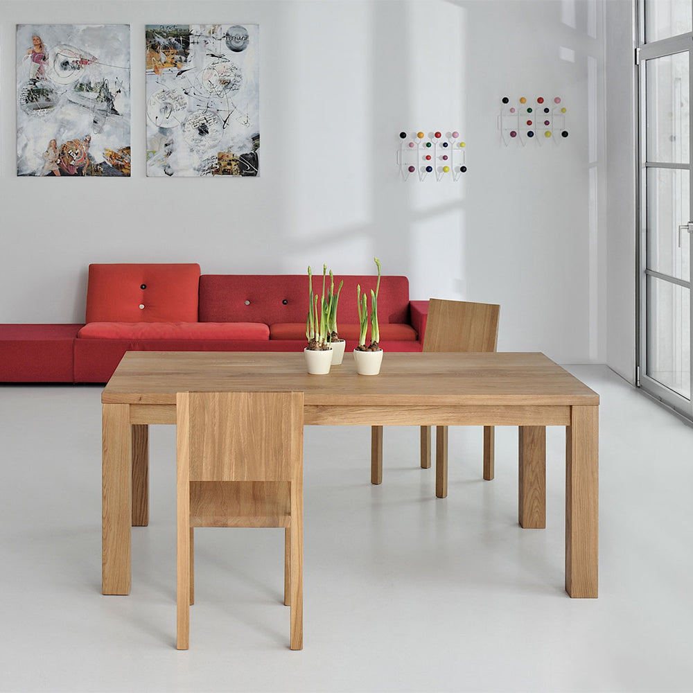 journeyman dining table in oak,  four corner legs, simple top.shown in modern dining room.