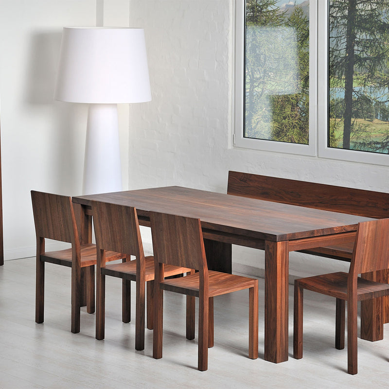 journeyman dining table in walnut,  shown in modern dining room with walnut chairs