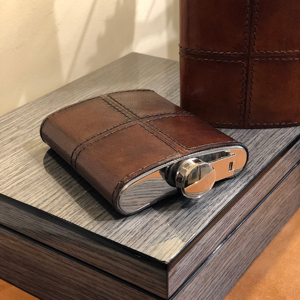 leather stitched cover on a stainless steel hip flask,