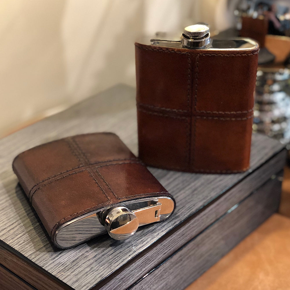 Brown leather stitched cover on a stainless steel hip flask,