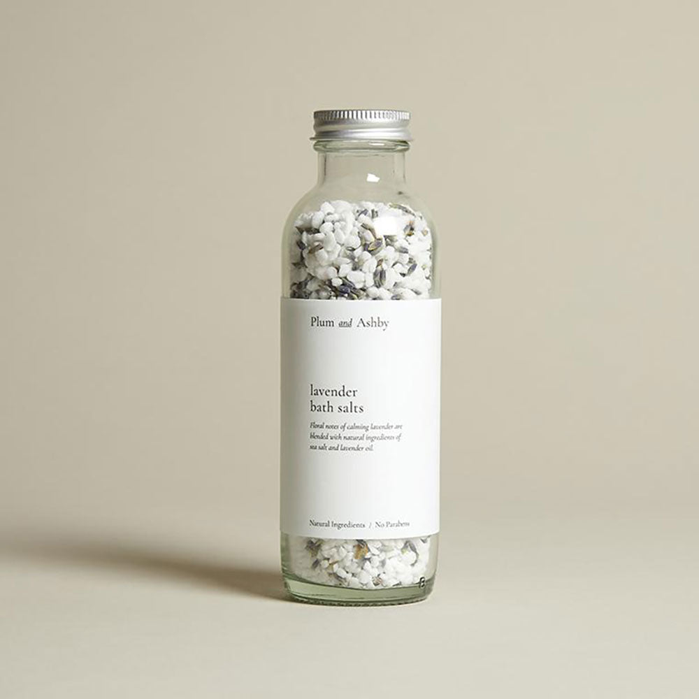clear glass bottle of salts mixed with lavender flower. white label, silver screw cap