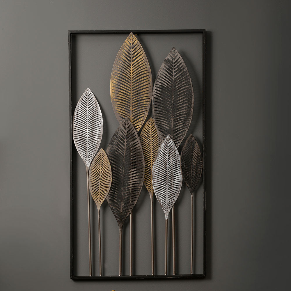 wall mounted art piece with skeletal metal leaves in various shades of gold grey white and black.