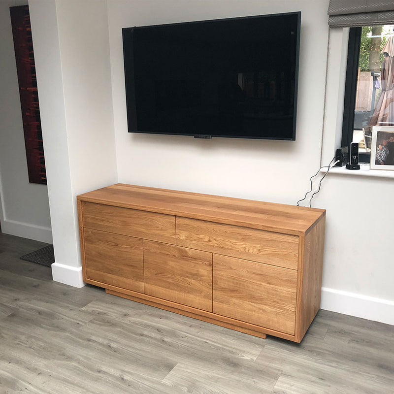 Linn sideboard with flat handle less front. two drawers over three doors- shown under tv on wall.