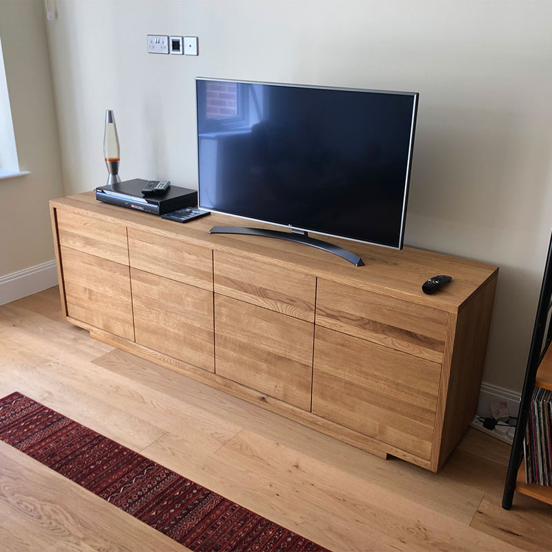 Linn sideboard with flat handle less front. four drawers over four doors- shown with tv on stand sitting on it,