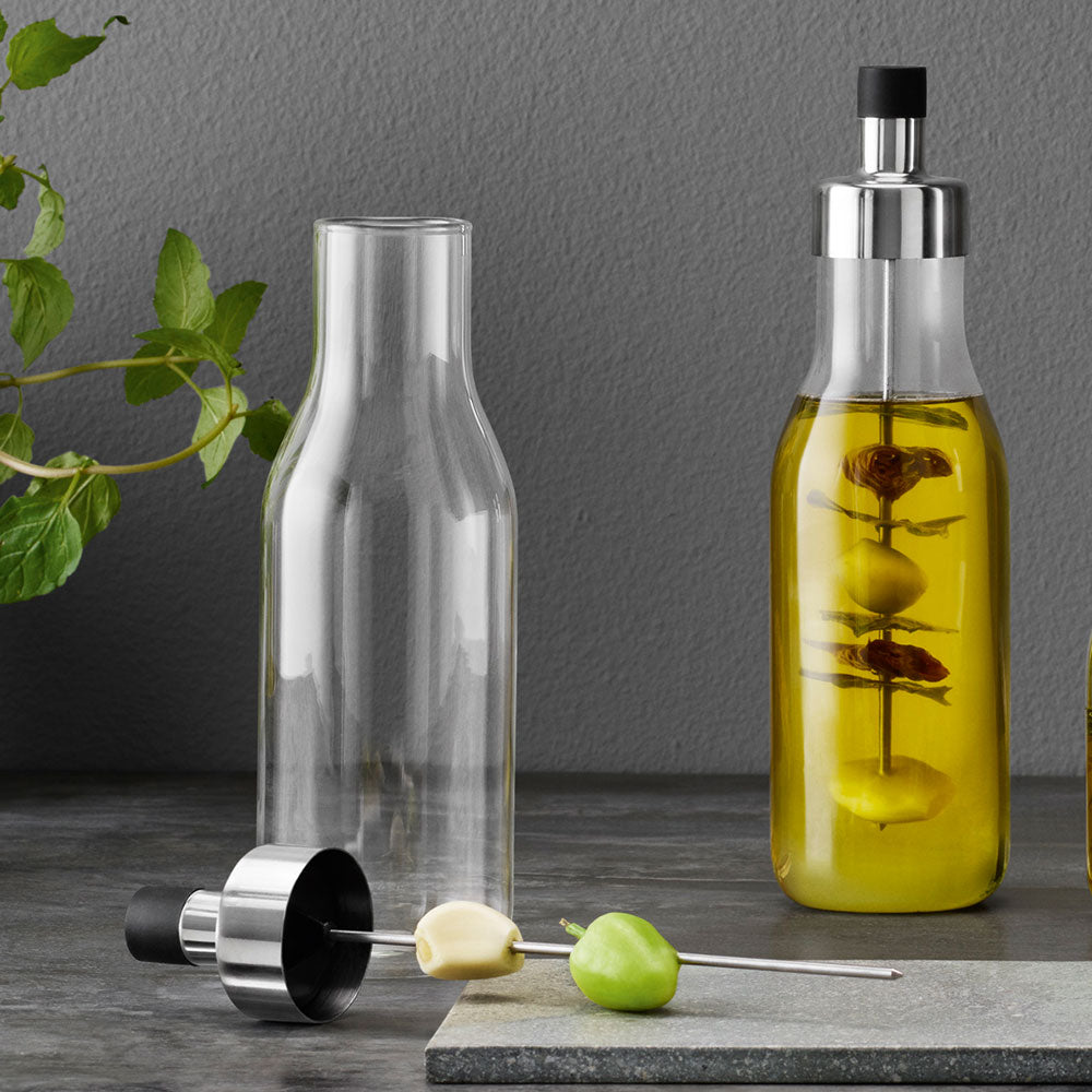 glassbottle with pouring lid ofr oils and dressings, shown open with garlic and olives on the stake ready to flavour oil