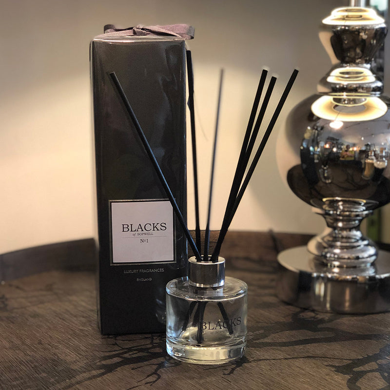 No1 diffuser in clear glass container , black reeds , next to black box packaging with black ribbon.