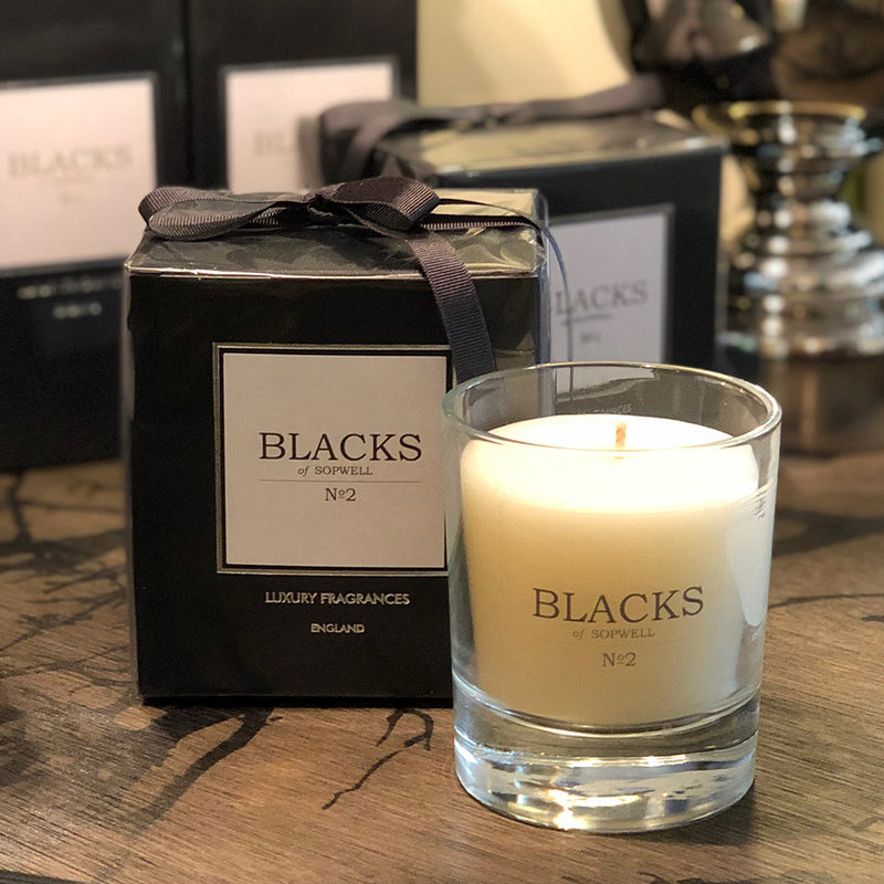 No2 perfumed candle in clear glass jar. white wax. shown with black packaging box, tied with a charcoal grey ribbon.