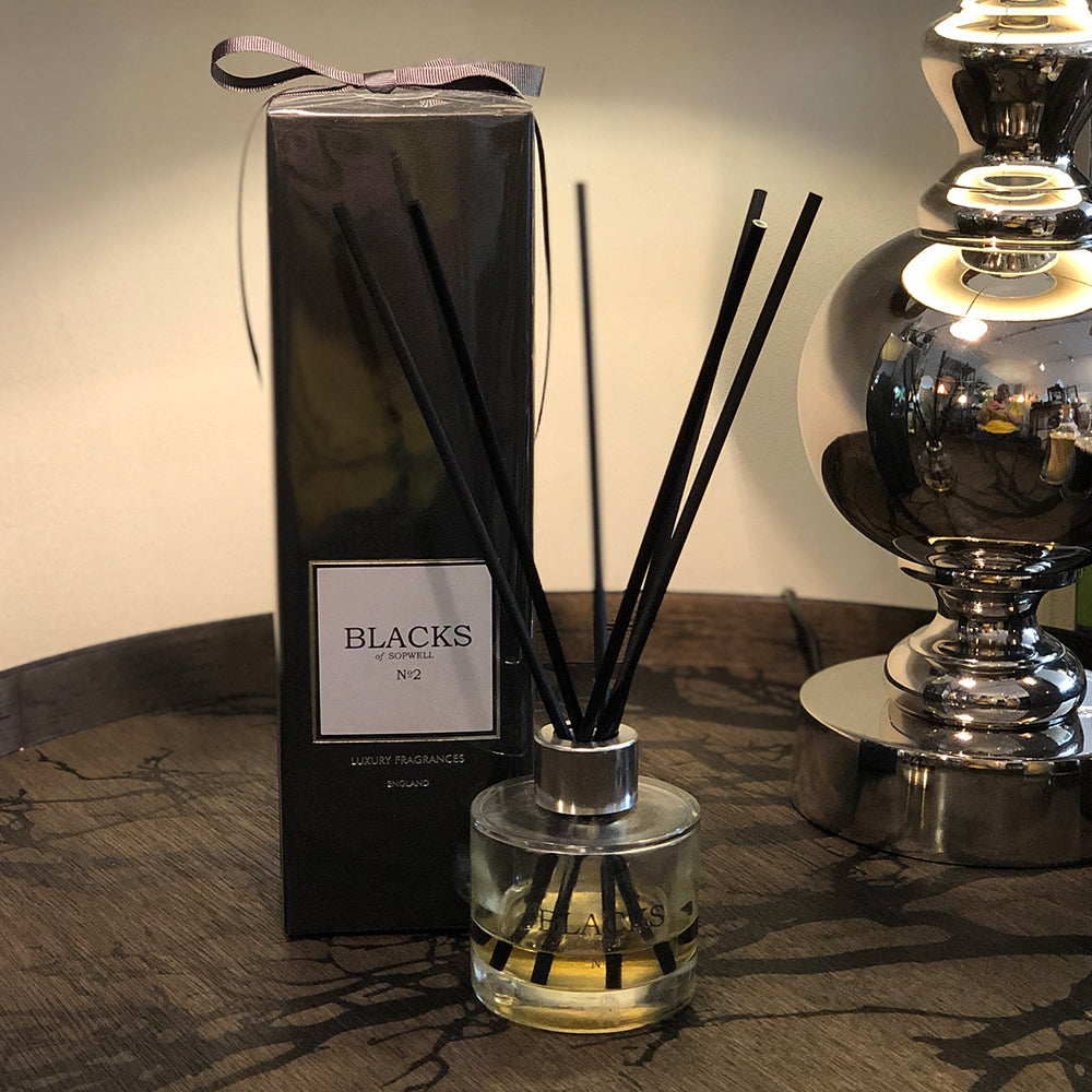No2 diffuser glass container with black reeds. shown next to black boxed package with charcoal ribbon.