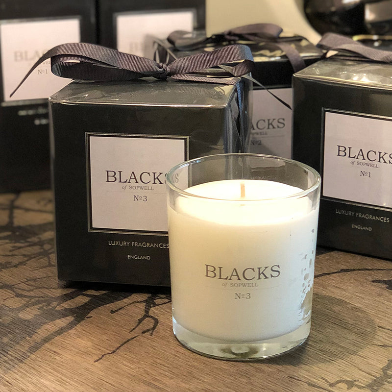 clear glass jar candle with white wax, next to black packaging topped with ribbon