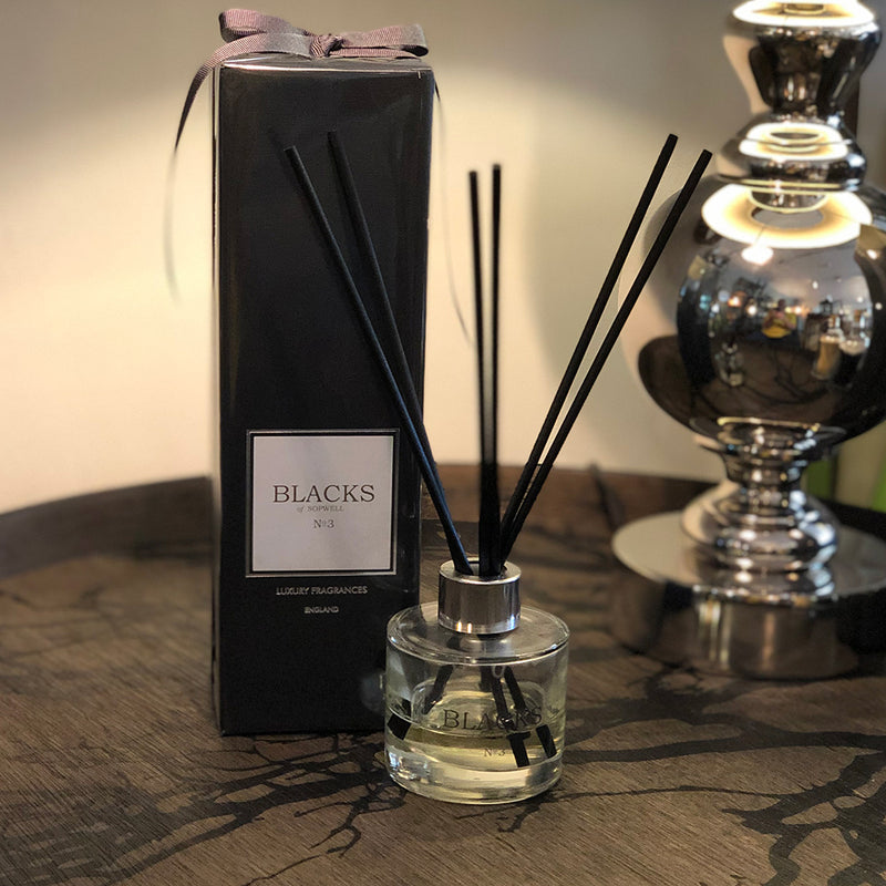no3 scented room diffuser, in clear glass container, next to black box packaging.