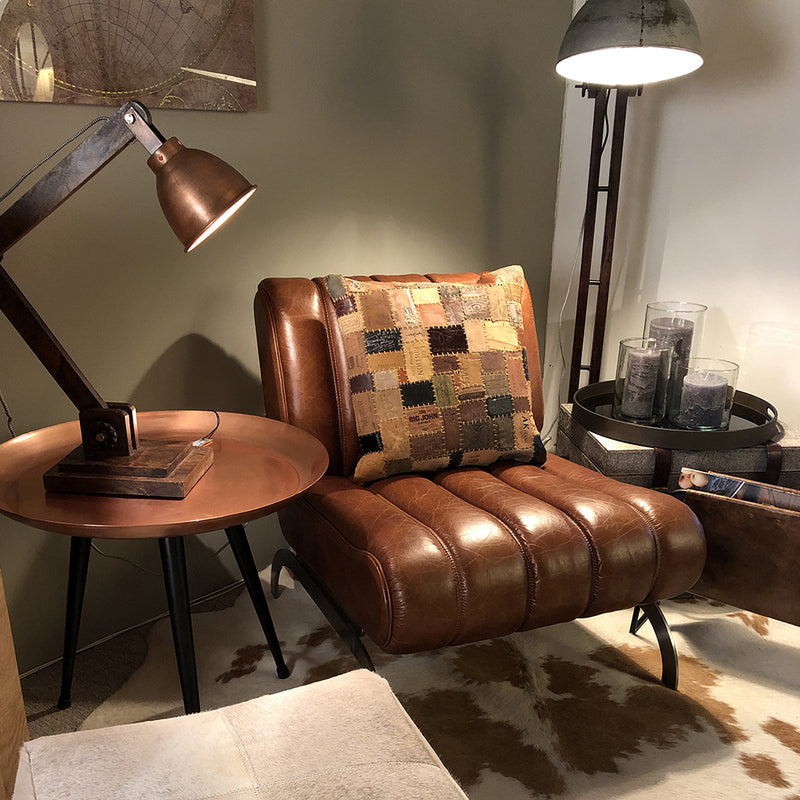 Tan leather chair, with stitched back and seat. shown with vintage leather cushions and copper acccesories.