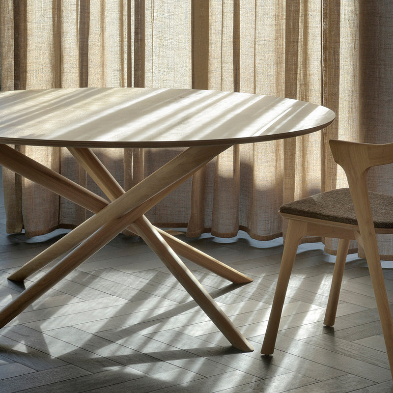round oak dining table next to a window with light streaming across the table