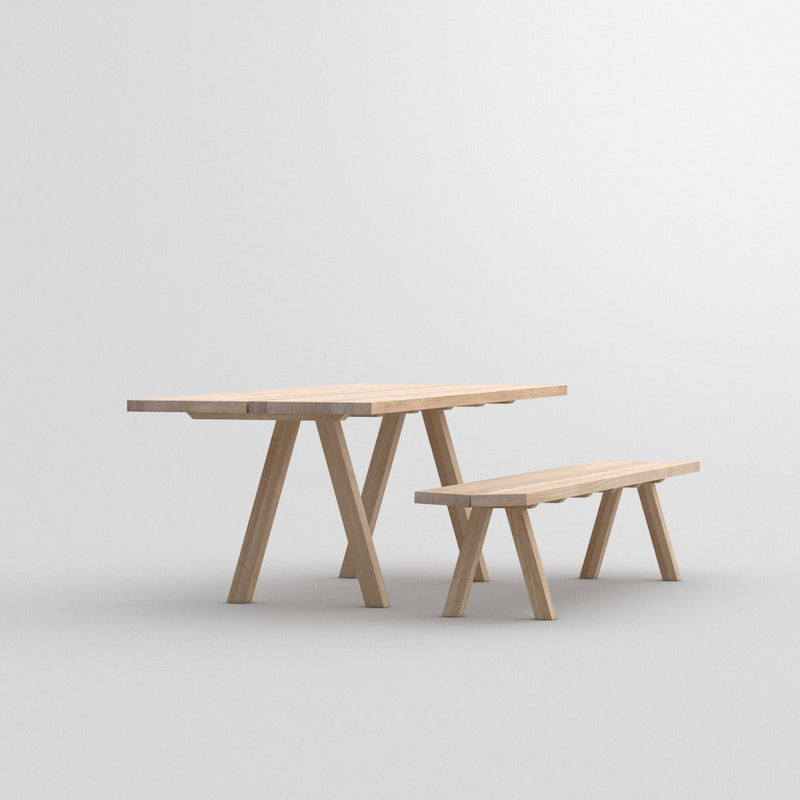 Facile dining table in oak with accompanying bench,front view of legs