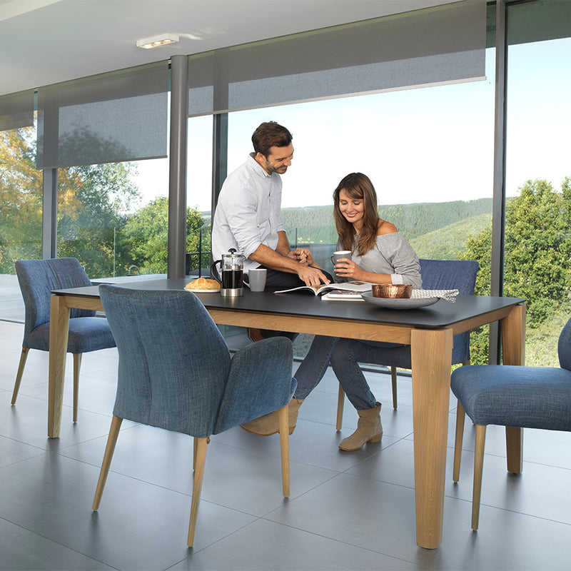 fenix top oxford table with couple chatting in front of large windows