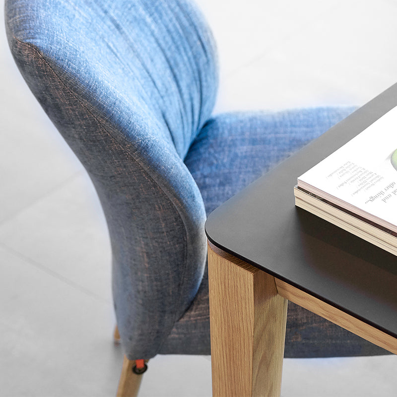close up showing rounded table top and leg profile and a blue chair