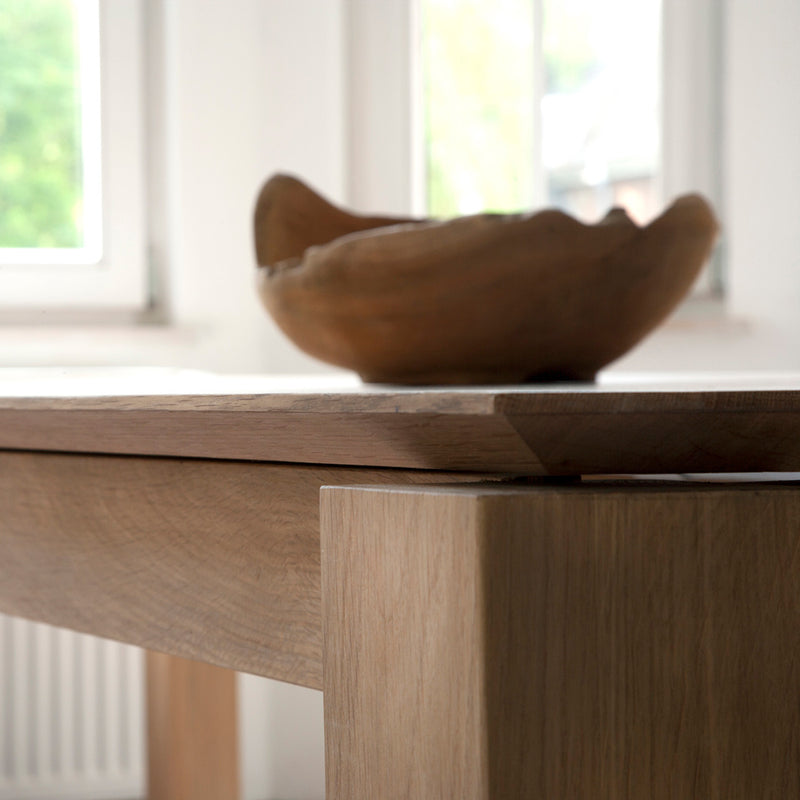 oak dining table showing the angle to the underside of the planar table top, with oak bowl