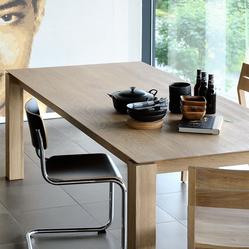 Oak planar fixed table styled with bottles and plates for entertaining friends