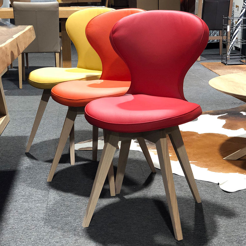 R1 leather dining chair with oak legs, shown in red orange and yellow options